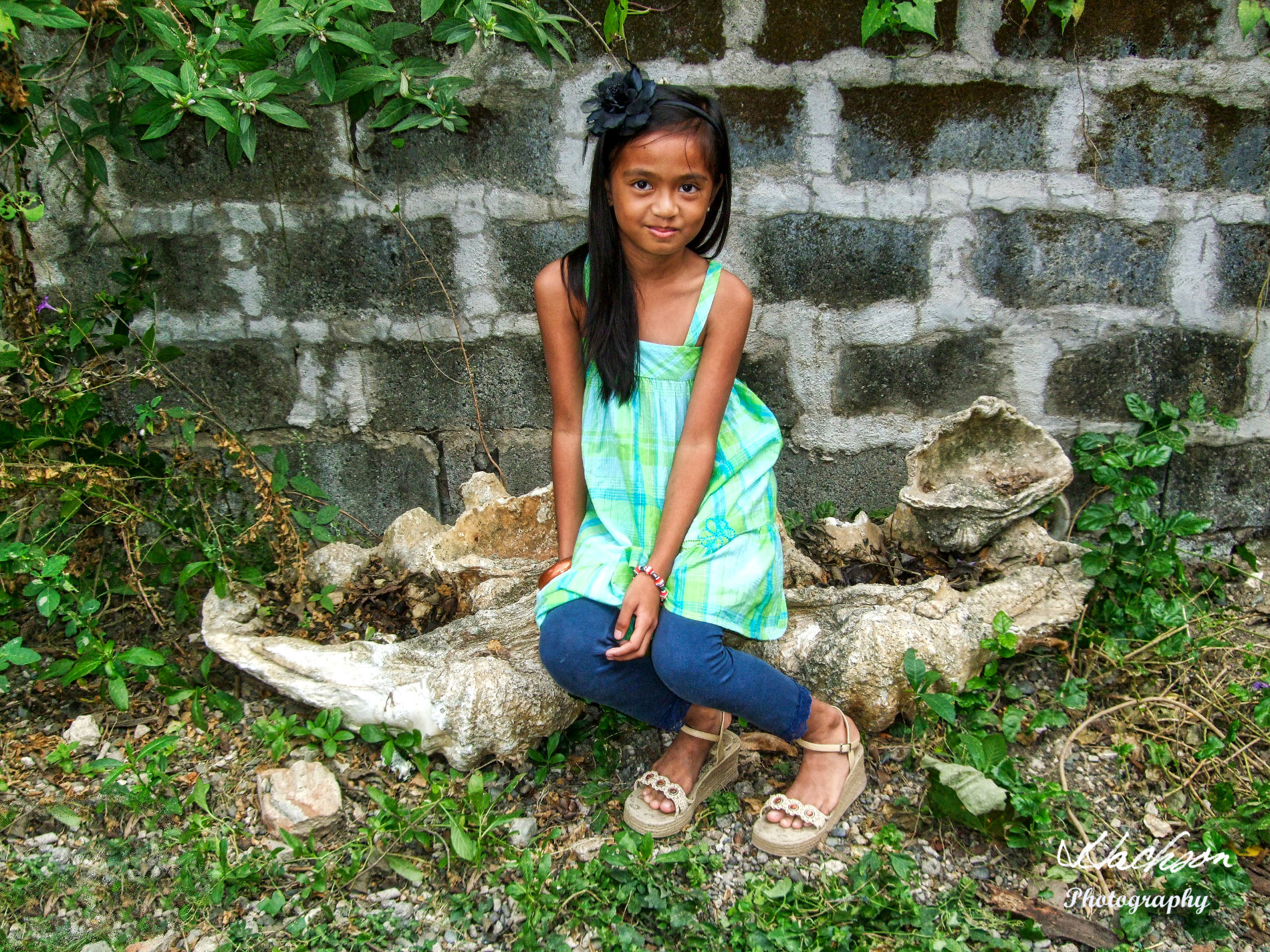 Young girl sitting on Philippine fossilized giant clam