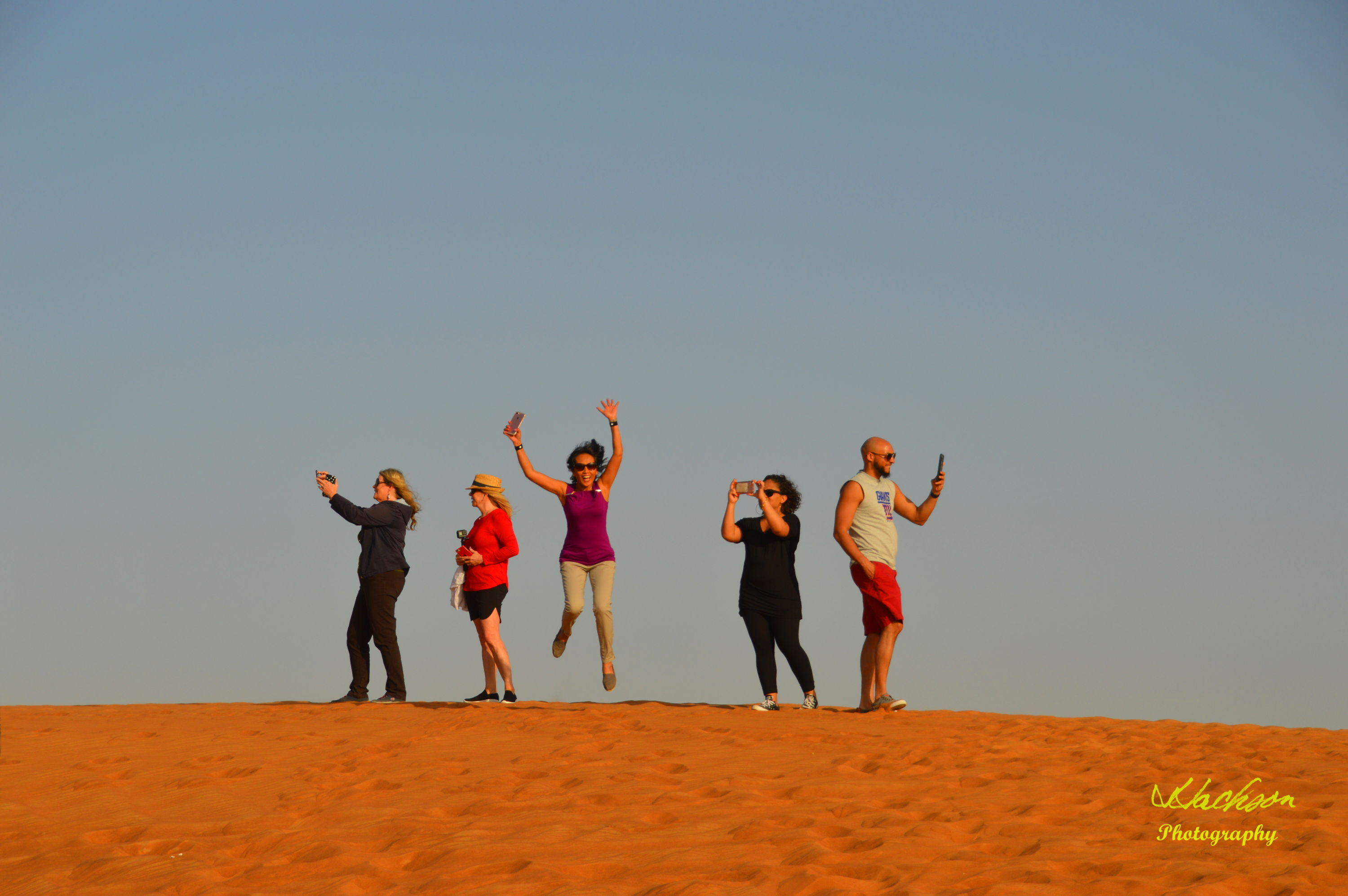 Photo of people jumping on a Dubai sand dune