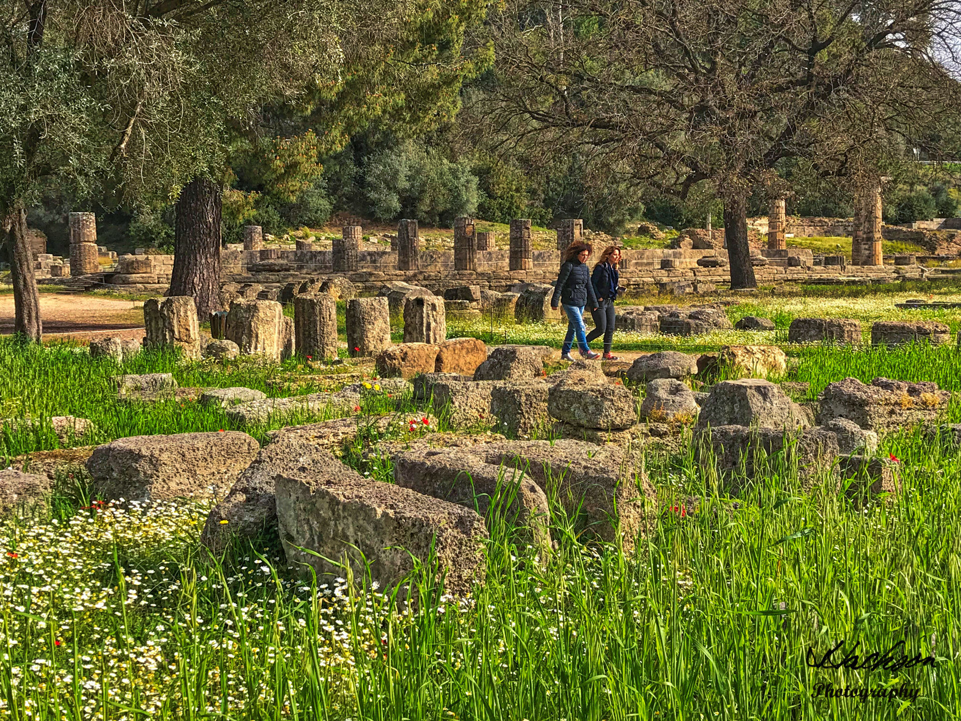 Photo of people walking among the ruins at Olympia